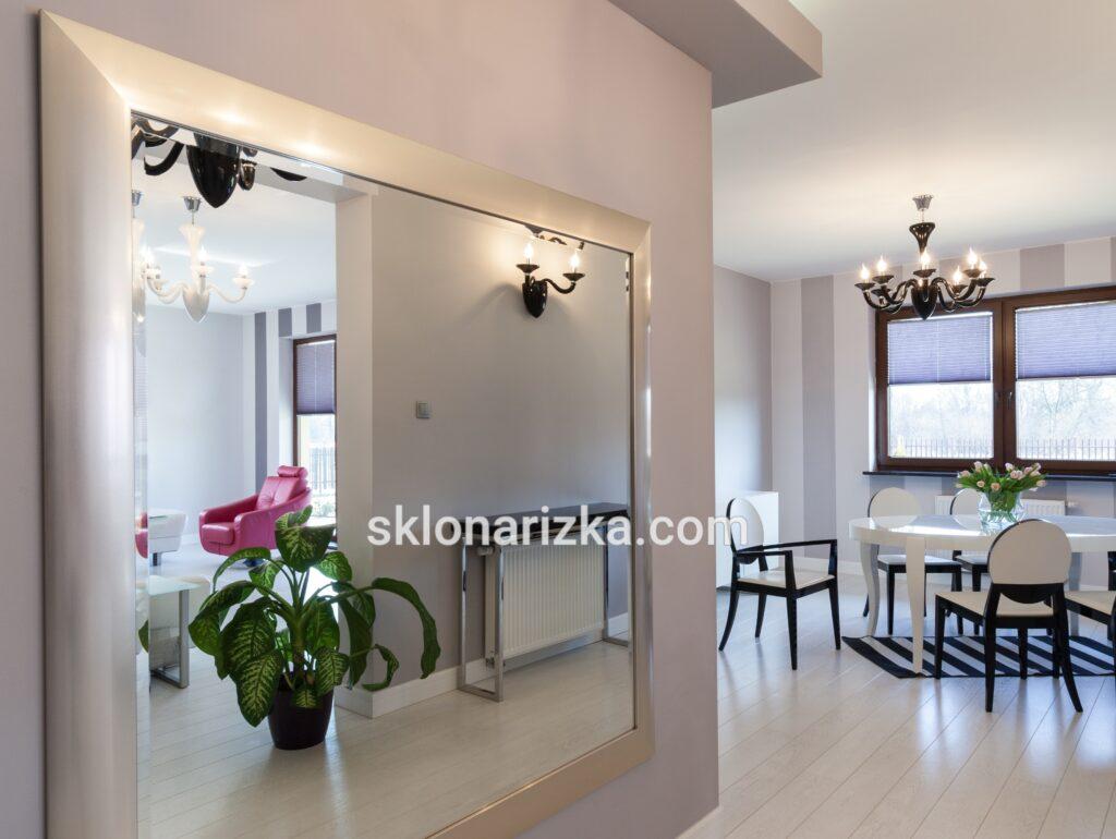 Велике срібне дзеркало з фацетом і в широкій багетній рамі у вітальні_